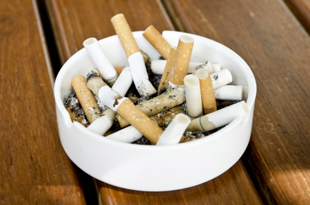 Cigarette in ceramic bin on wood table background photo