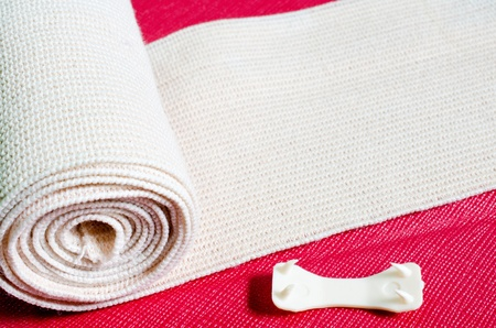 Roll of the elastic bandage against with Cherry color background