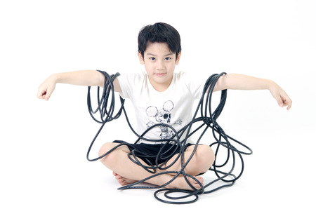 Portrait of Asian cute boy with electric wire cable on white background .  photo