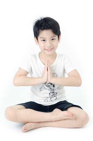 Portrait of Asian cute boy practicing yoga on white background .  photo