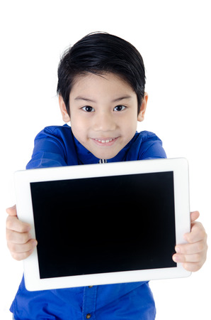 Little asian boy smiles with tablet computer on isolated background
