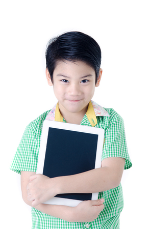 Little asian boy smiles with tablet computer on isolated background photo