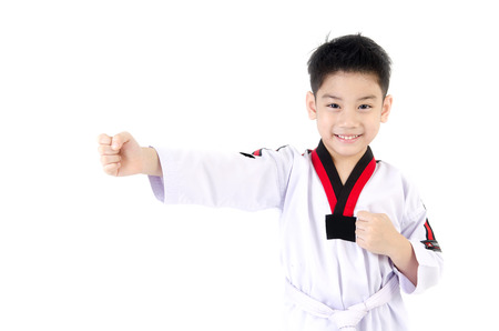 little asian smile boy in a Taekwondo uniform with a white sash on a white background Banco de Imagens