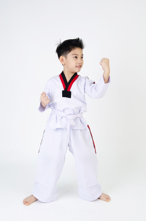 little smile boy in a Taekwondo uniform with a white sash on a gray background