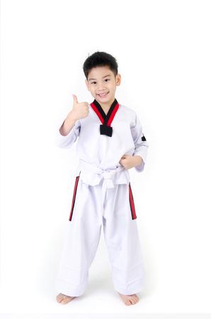 little smile boy in a Taekwondo uniform with a white sash on a white background Stock Photo
