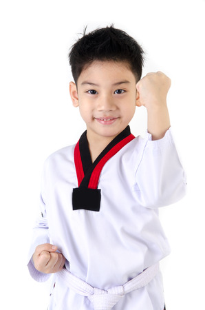little smile boy in a Taekwondo suit with a white sash on a white background Banco de Imagens