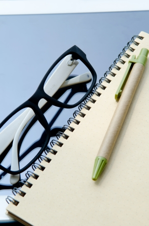 Office supplies Notebook paper tablet and glasses .  photo