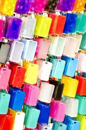 MultiColor plastic mobile phone cases on hangers .