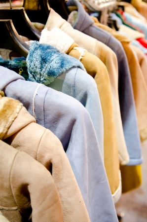 female coat clothes hanging on clothes rack