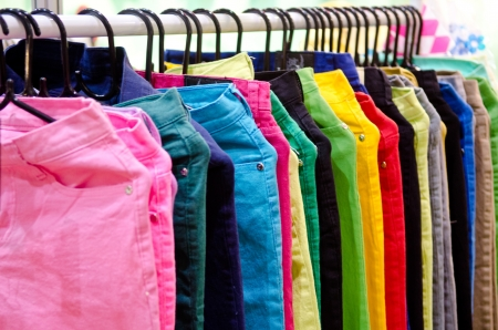 Stack colorful jean with hangers .