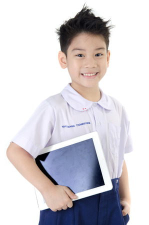 Little asian boy in student's uniform with tablet computer on isolated background