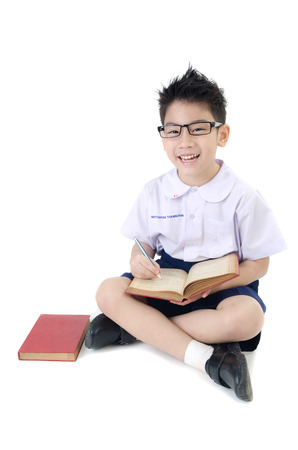 Asian child boy in students uniform with red book on isolated background