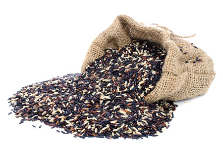 Black Rice pile in Gunny bag with white isolate background