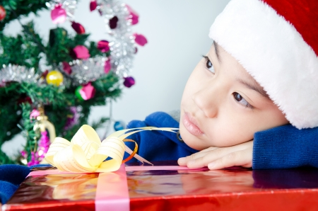 Portrait of Asian cute boy  in christmas hat with red gift box .  photo