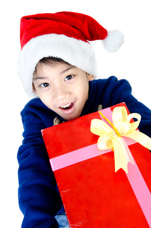 Portrait of Asian cute boy with red gift box in christmas hat isolate on white background    photo