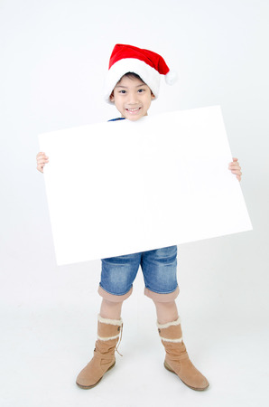 Portrait of Asian cute boy in christmas hat with white board for add your text    photo