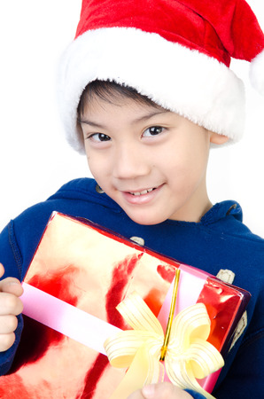 Portrait of Asian cute boy with red giftbox in christmas hat photo