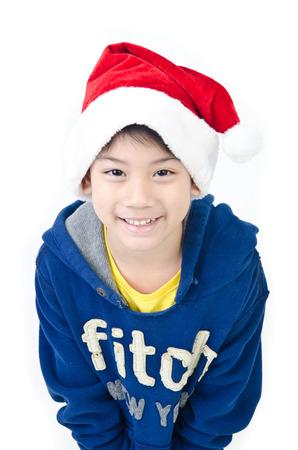 Portrait of Asian happy boy in santa hat on white background    photo