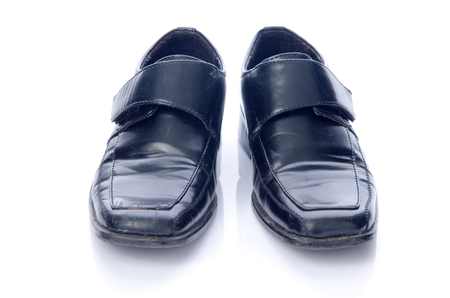 Old black shoes and shadow isolate on white . Stock Photo - 24389925