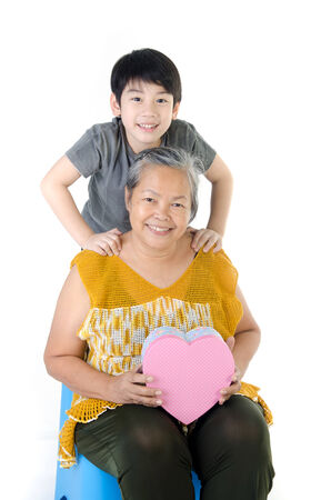 Asian Grandmother and child with Heart giftbox on white background . photo