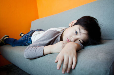 Asian boy sleeping on a Sofa bench with hand under his forehead photo