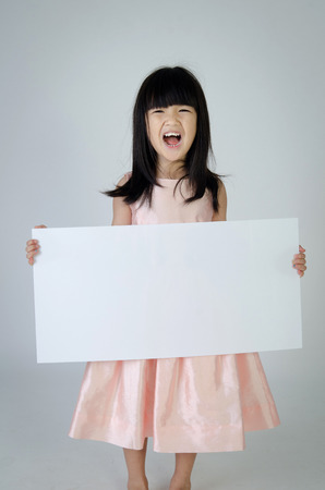 Portrait of young Asian girl holding blank billboard on gray background