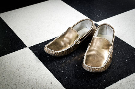 Old Golden shoes on black and white floor background .  photo