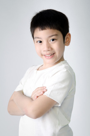 Portrait of smile asian cute boy on gray background . Studio fashion portrait. Banque d'images
