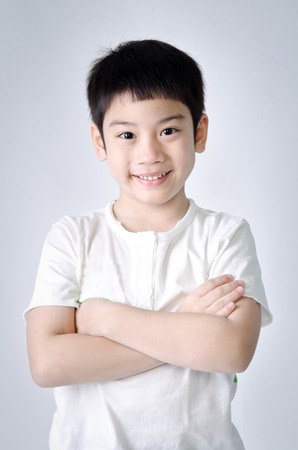 Portrait of smile asian cute boy on gray background . Studio fashion portrait. Stock Photo