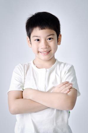 Portrait of smile asian cute boy on gray background . Studio fashion portrait. Stock Photo