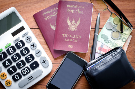 Thailand Passport with currency , calculator and Cell Phone on a Wood Background. photo