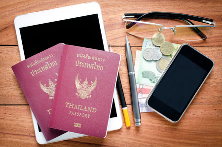 Thailand Passport with currency ,Glasses and Cell Phone on a Wood Background. photo