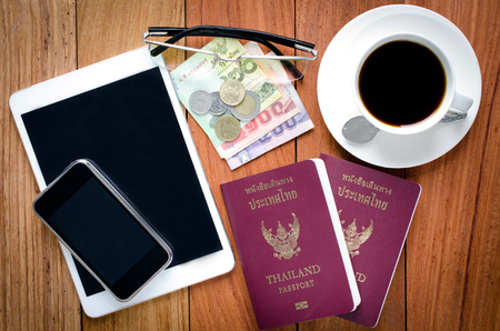 Thailand Passport with currency , Coffee and Cell Phone on a Wood Background. photo