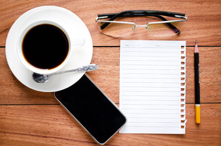 empty notebook and a cup of coffee on the wooden desk background photo