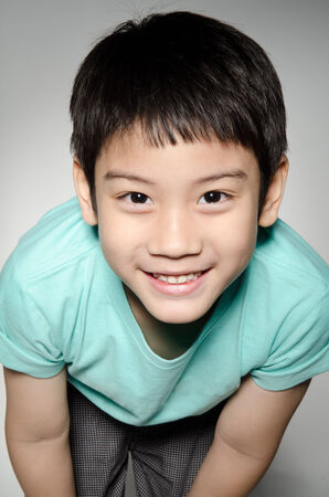 Portrade Of asian cute boy on gray background .