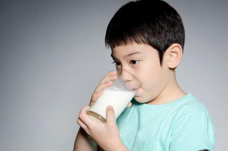Portrait of Little asian boy drinking a glass of milk on gray background . Banco de Imagens