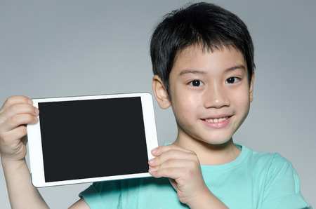Little asian boy smiles with tablet computer on gray background
