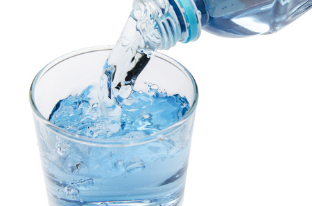 emptied: pure water is emptied into a glass of water from bottle. fresh drinking water Stock Photo