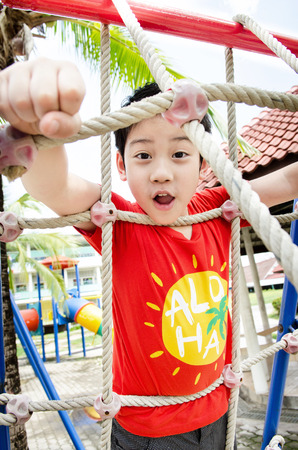 Happy asian cute boy playing on playground .  photo
