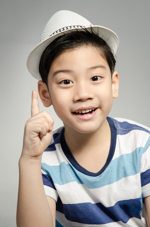 Portrait of asian cute boy with white hat on gray background .