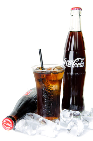 coke bottle: BANGKOK, THAILAND - JULY 14, 2014  Cold Classic Coke Bottle on a white background with glass and ice Editorial