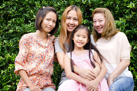 Group of Asian family mother sister and daughter  with green leaf background .  photo