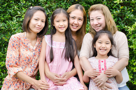 Group of Asian family mother daughter with green leaf background . photo