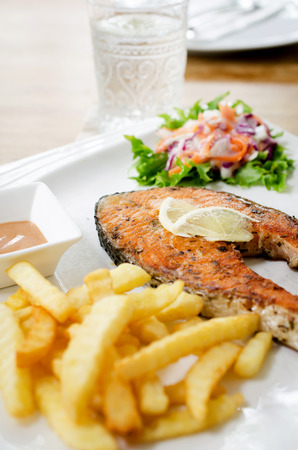 grilled salmon steak served with salad, chips, peas and lemon slices. photo