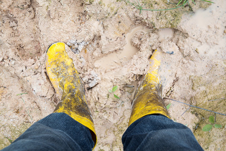 muddy clothes: Human leg with Yelkow Muddy rubber boots on wet silt Stock Photo