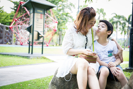 Asian woman talking about wit your son in the park