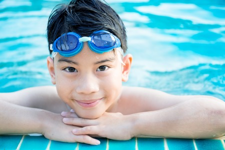 Portrait of happy asian little boy playing in the pool Banco de Imagens