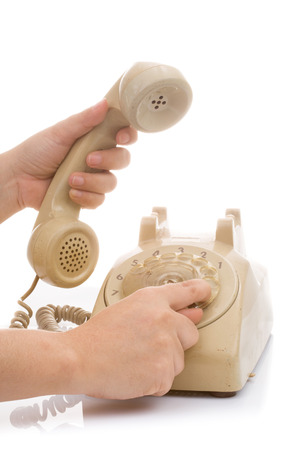 Hand hold vintage telephone and press number on white background Stock Photo