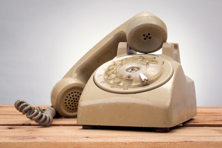 handed: vintage telephone on wood background