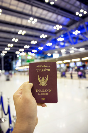 customs official: hand holding Thailand passport with gate of airport background Stock Photo